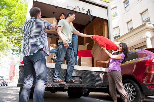 Trois personnes qui chargent un camion de déménagement