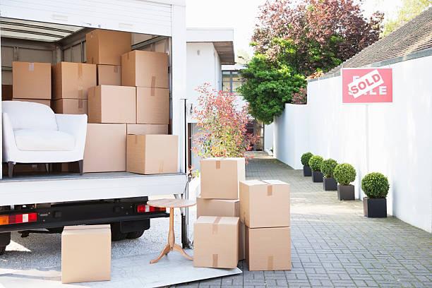 """Camion de déménagement plein de carton devant une maison qui affiche """"vendue"""""""